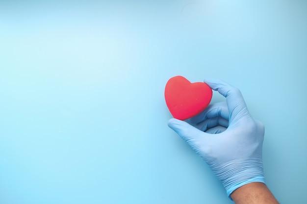 Mão de homem em luvas protetoras segurando um coração vermelho em azul.