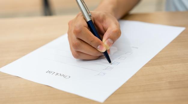 Mão de homem empregado usando caneta para lista de verificação