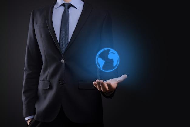 Mão de homem empresário segurando o ícone da terra, globo digital.