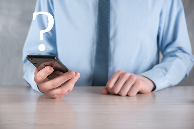 Mão de homem empresário segurar interface de interrogação assina web. pergunte online, conceito de faq, onde, quando, como e por que, busque informações na internet.