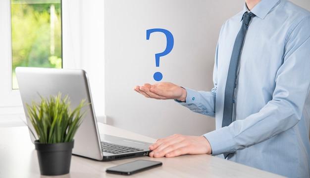 Mão de homem empresário segure pontos de interrogação interface assinam web. pergunte online, conceito de faq, onde, quando, como e por que, busque informações na internet.