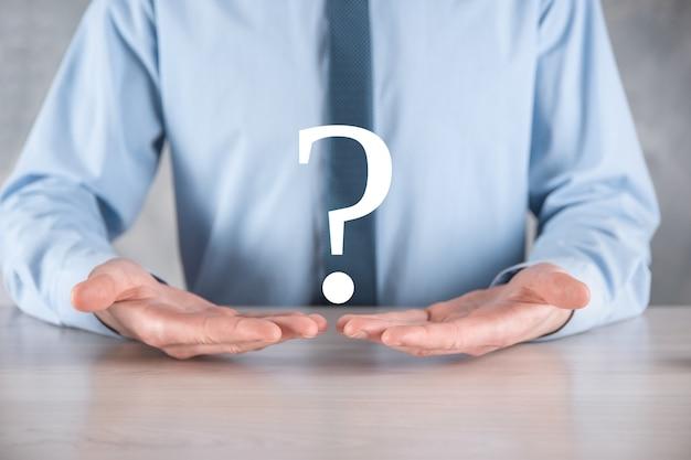 Mão de homem empresário segure pontos de interrogação interface assinam web. pergunte online, conceito de faq, onde, quando, como e por que, busque informações na internet