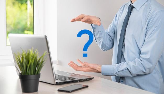 Mão de homem empresário segure pontos de interrogação interface assinam web. pergunte online, conceito de faq, onde, quando, como e por que, pesquise informações na internet