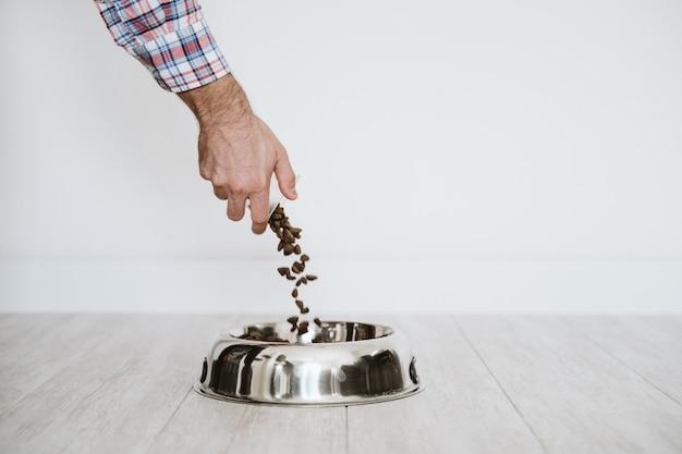 Mão de homem, enchendo uma tigela de comida de cachorro em casa