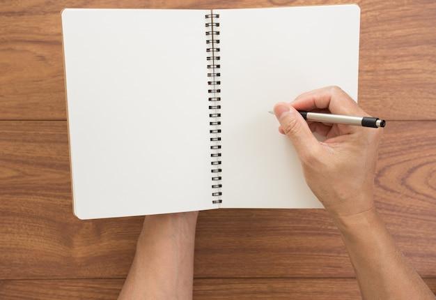 Mão de homem escrevendo caderno sobre fundo de madeira