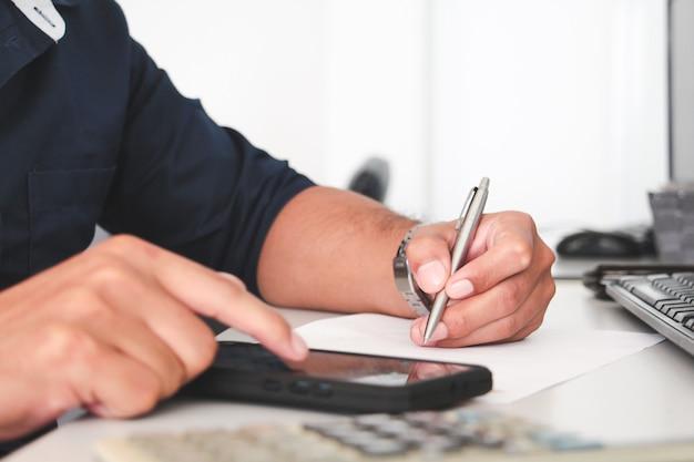 Mão de homem escrevendo com caneta e mão touchon tela de telefone inteligente. negócios e conceito de escritório de trabalho. conceito de trabalho. usando smartphone. se comunica com smartphone.