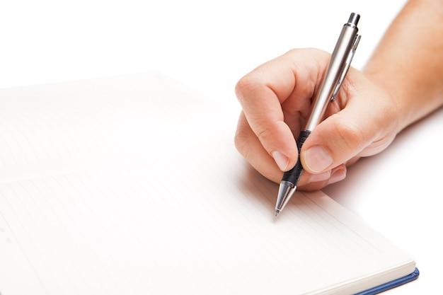 Mão de homem escrevendo em livro aberto, isolado no branco