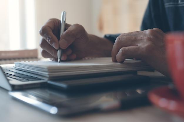 Mão de homem escrevendo em um caderno de papel e trabalhando em um laptop no escritório