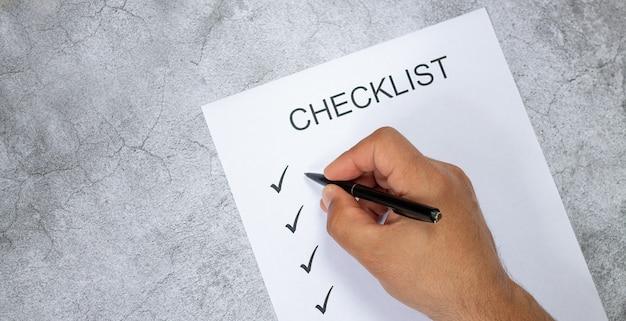Mão de homem, escrevendo na lista de verificação com caneta preta na mesa de pedra