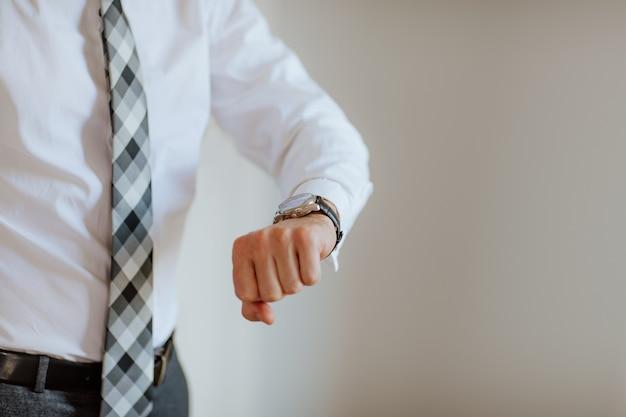 Mão de homem levantada em camisa branca e gravata cinza mostrando as horas