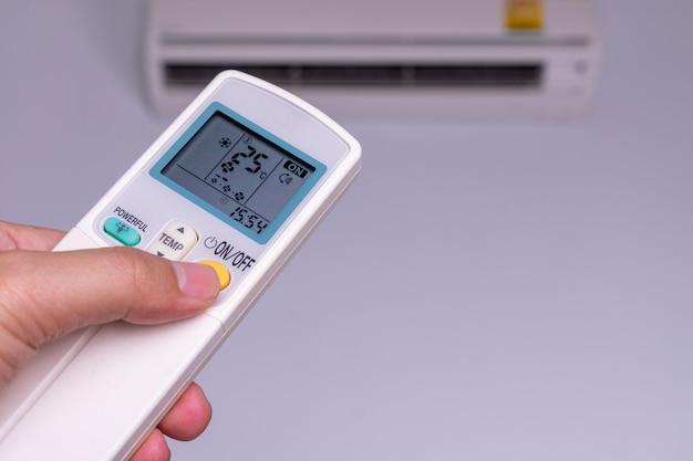 Mão de homem ligar o condicionador de ar 25 graus celsius. economia de energia.