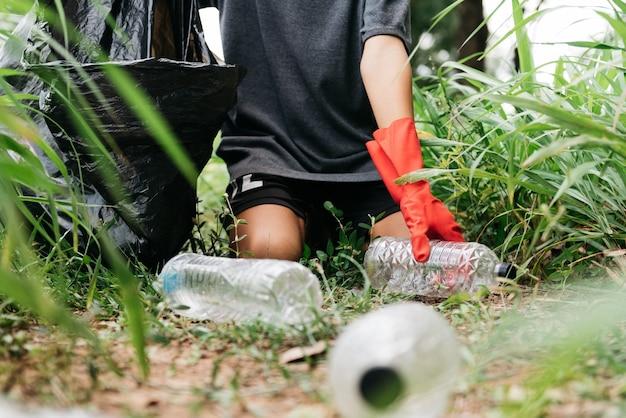 Mão de homem menino pegar uma garrafa de plástico na floresta. conservação da natureza e conceito de meio ambiente.