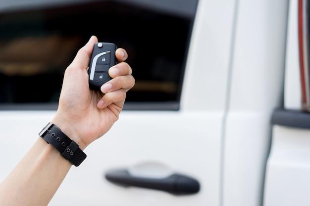 Mão de homem motorista segurando keyless de carro autônomo para desbloquear através da tecnologia sem fio