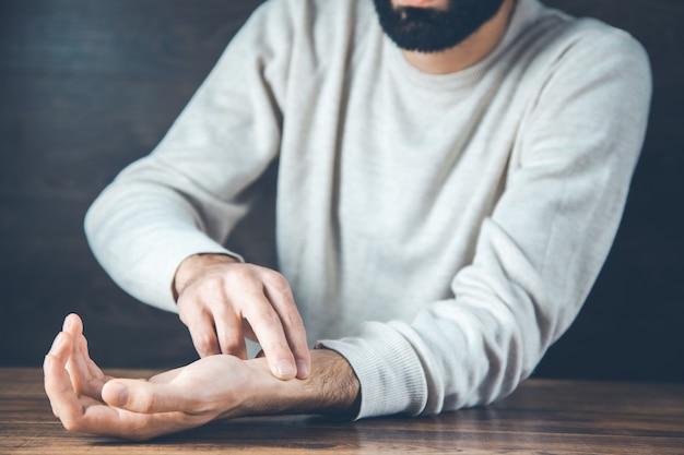 Mão de homem no pulso em fundo escuro