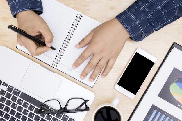 Mão de homem no teclado do laptop com monitor de tela em branco, homem trabalhando negócios trabalhando em madeira