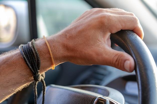 Mão de homem no volante de um carro. dentro do carro, mãos masculinas dirigindo. conceito de viagens, copie o espaço para o seu texto, close-up. motorista, cara. mão cortada de homem no volante preto, um automóvel moderno