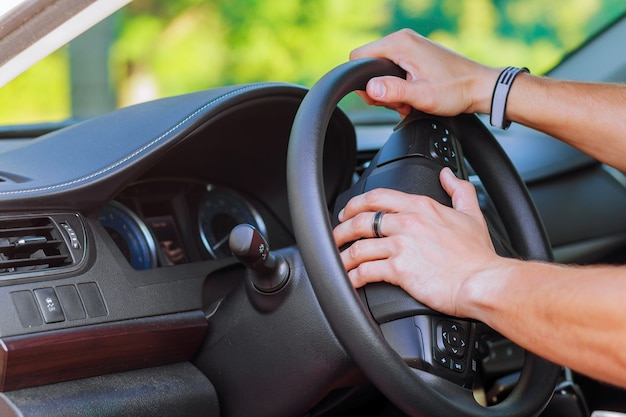 Mão de homem no volante de um carro