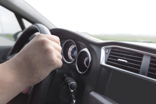 Mão de homem no volante no salão de um carro moderno