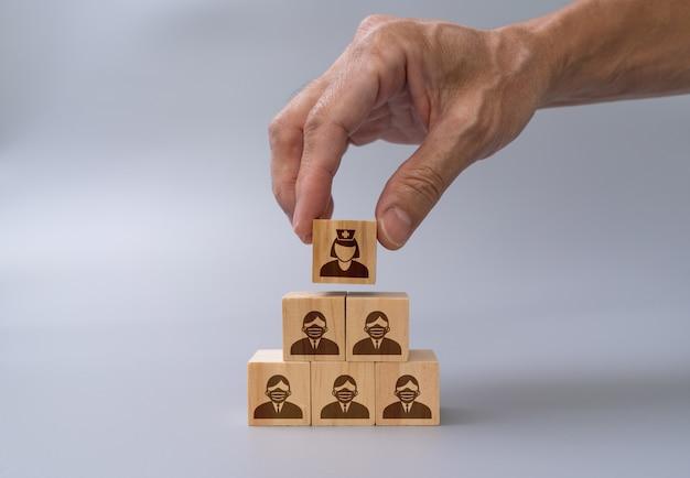 Mão de homem, organizando os blocos de madeira com empilhamento de ícones de saúde e médicos, conceito de seguro médico