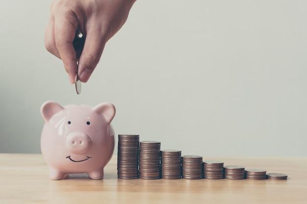 Mão de homem ou mulher colocando moedas no cofrinho com pilha de dinheiro