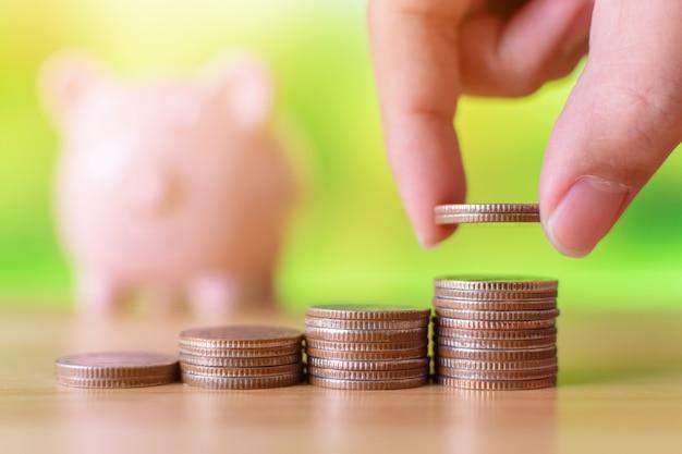 Mão de homem ou mulher colocando moedas pilha de dinheiro com cofrinho