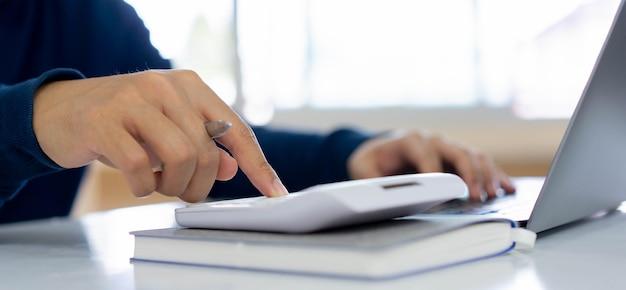 Mão de homem pressionando calculadora para calcular estimativa de custo