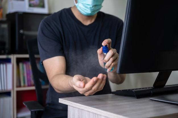 Mão de homem pulverizando álcool 70% ou desinfetante