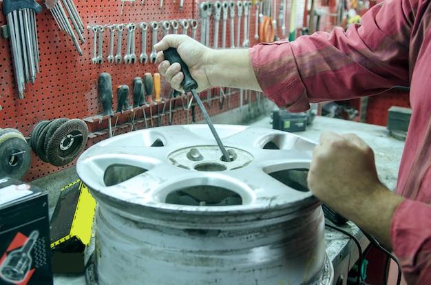 Mão de homem reparar roda de metal velho carro usando chave de fenda. preparar para a fixação de pneu de carro