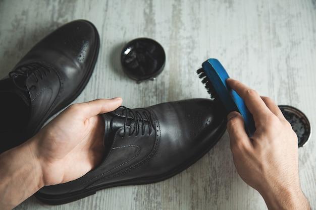 Mão de homem sapatos de couro e acessórios para cuidar de sapatos