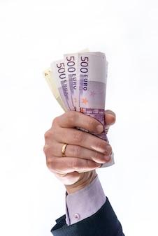 Mão de homem segura ou dinheiro dado isolado no fundo branco. moeda euro com notas de 500 e 200 euros