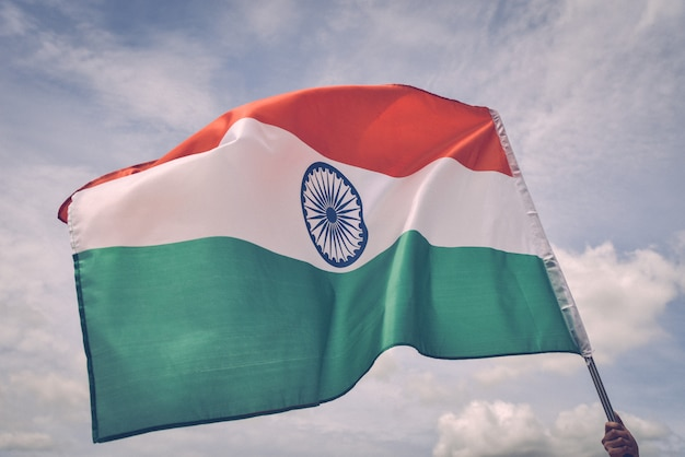 Mão de homem segurando a bandeira da índia no céu azul