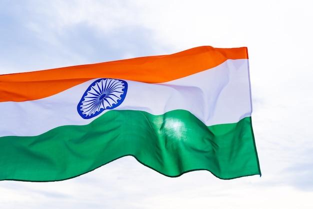 Mão de homem segurando a bandeira da índia sobre o fundo do céu azul.