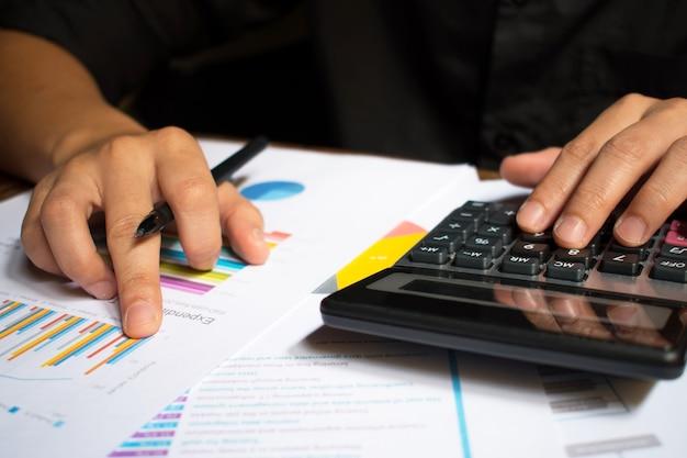 Mão de homem segurando a caneta e cálculo de números.