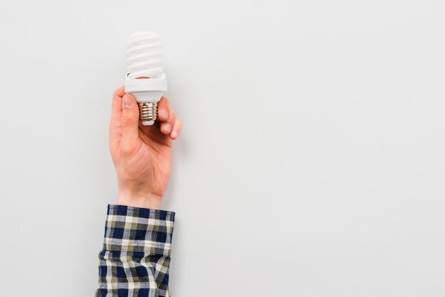 Mão de homem segurando a lâmpada de poupança de energia