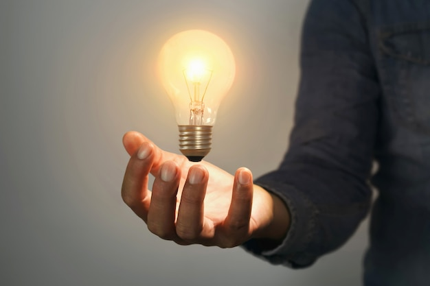 Mão de homem segurando a lâmpada no quarto