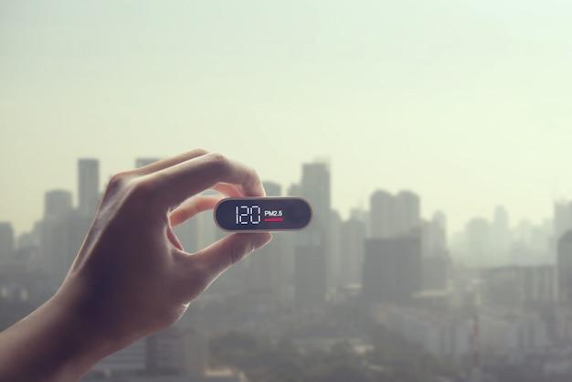 Mão de homem segurando a pm. detector sobre a cidade da poluição atmosférica