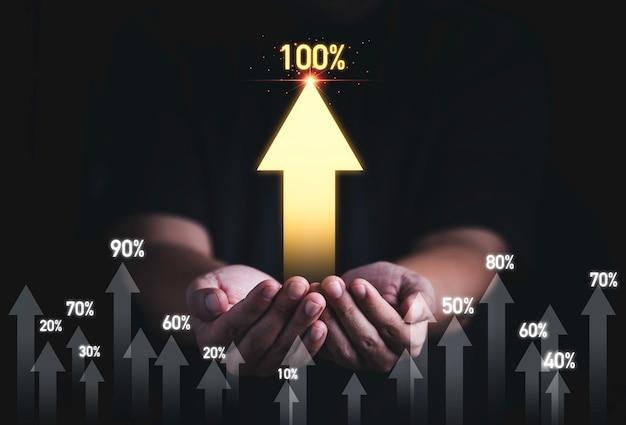 Mão de homem segurando a seta crescente dourada com porcentagem para o crescimento do desenvolvimento do lucro empresarial ao conceito de sucesso.