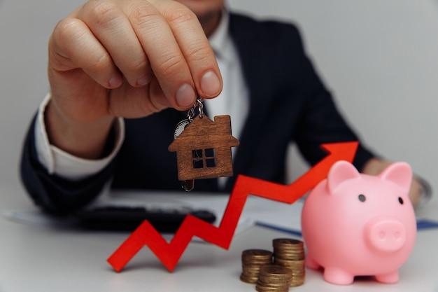 Mão de homem segurando a seta vermelha do close up da chave da casa e a pilha de moedas, dinheiro, investimento empresarial e conceito imobiliário
