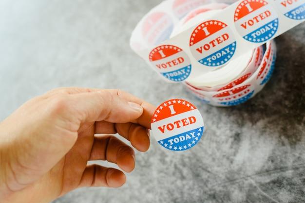 Mão de homem segurando adesivos de torcedor de eleições americanas