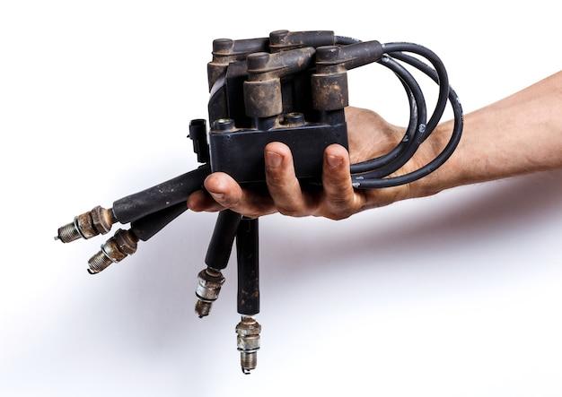 Mão de homem segurando as peças da ignição do carro