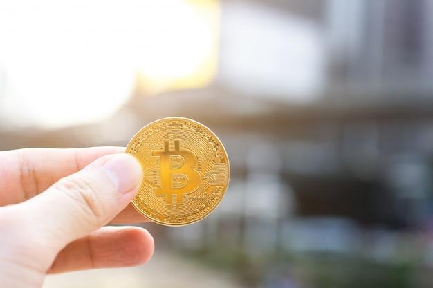 Mão de homem segurando bitcoin dourado