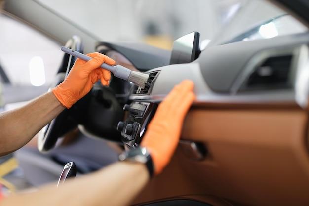 Mão de homem segurando blush cinza em luvas de proteção laranja