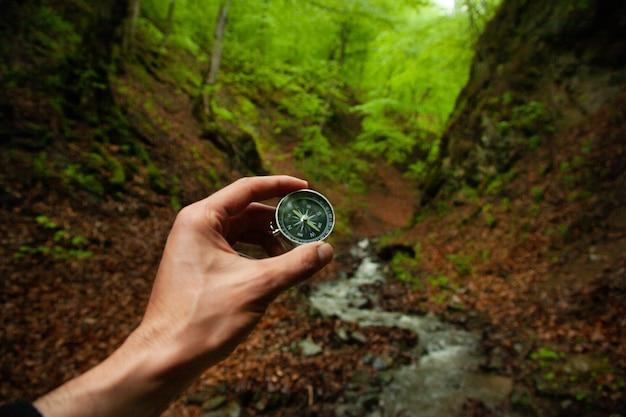 Mão de homem segurando bússola na floresta