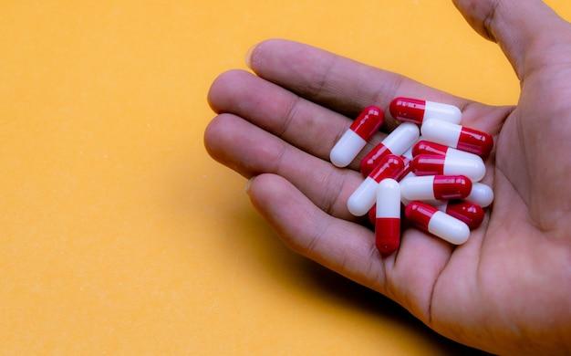 Mão de homem segurando cápsulas de redwhite em fundo amarelo. medicamento com receita farmacêutica