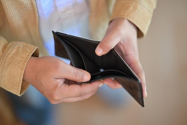 Mão de homem segurando carteira vazia