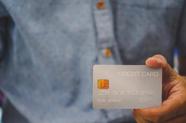Mão de homem segurando cartões de crédito. compras on-line por cartão de crédito. pedido de empréstimo de cartão de crédito.