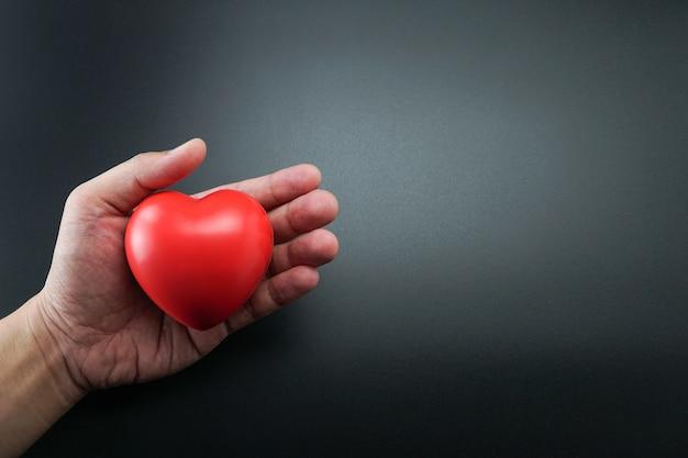 Mão de homem segurando coração vermelho