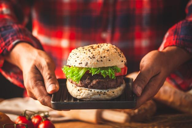 Mão de homem segurando delicioso hambúrguer caseiro com legumes frescos prontos para servir e comer