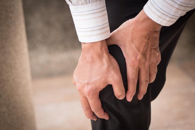 Mão de homem segurando dor nas articulações do joelho