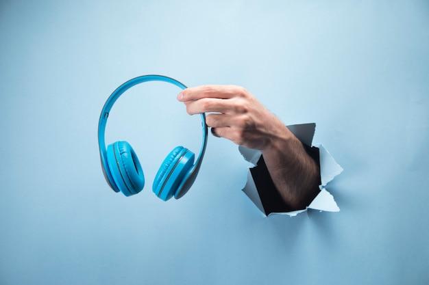 Mão de homem segurando fones de ouvido em cena azul